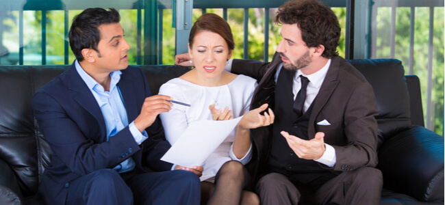 agent giving bad news to rich unhappy couple man woman sitting on black couch in house
